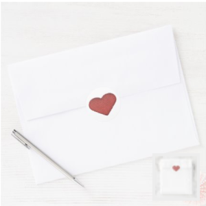 round white sticker with a red knit heart